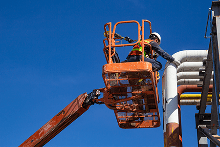 man on boom lift working on a pipe