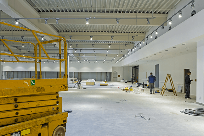 the inside of an building under construction with a yellow scissor lift not being used