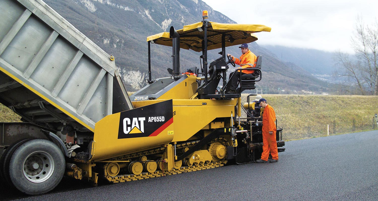 asphalt paver with worker on it