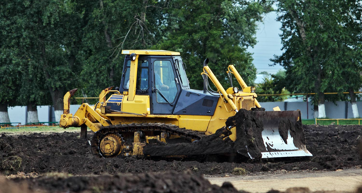 a bulldozer near a forest working on a site