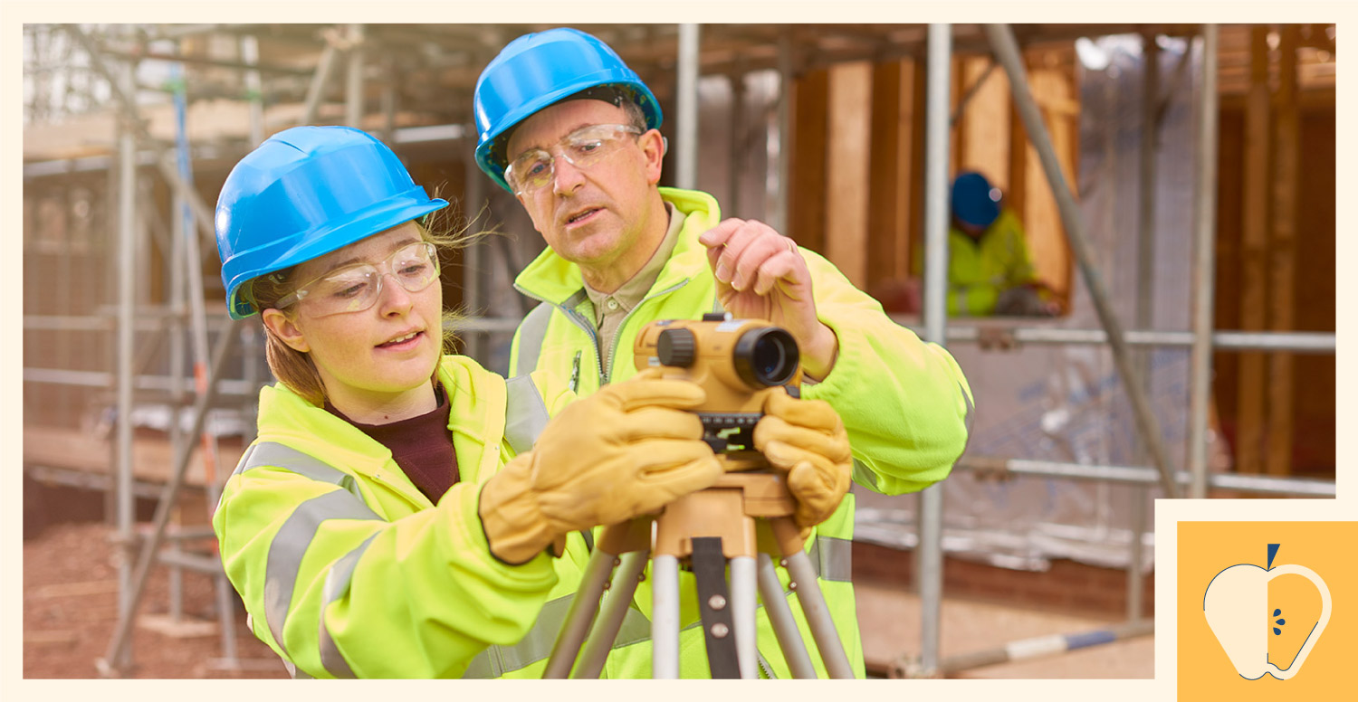 A junior construction worker learns how to operate a level from a senior construction worker.