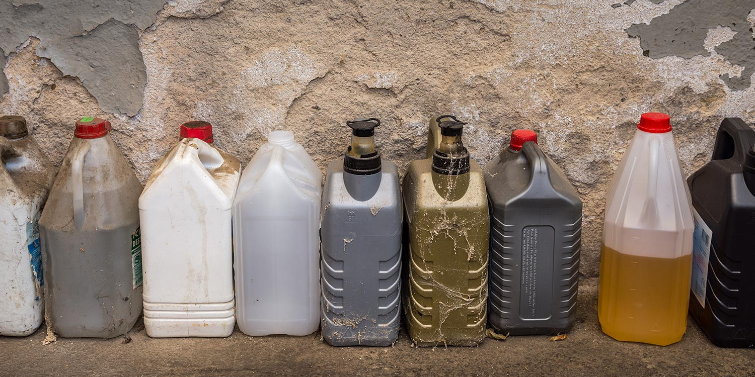 Various bottles and containers holding hazardous material like pesticides and motor oil.