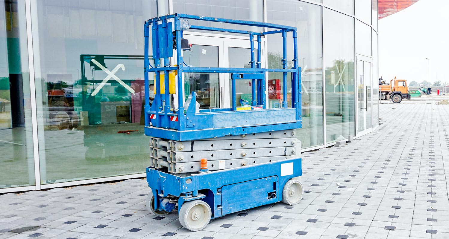 a blue scissor lift outside of a mall