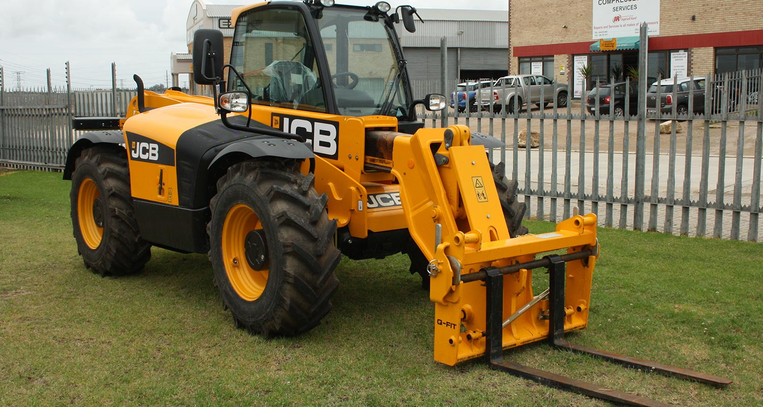 a telehandler on a green lawn next to a fence