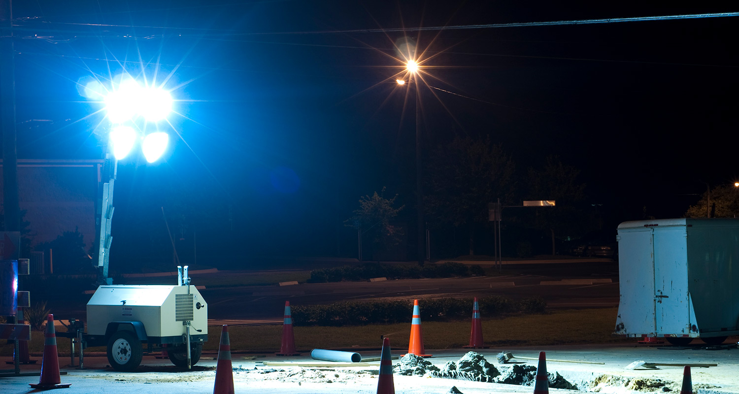 a towable light tower illuminating a construction site at night