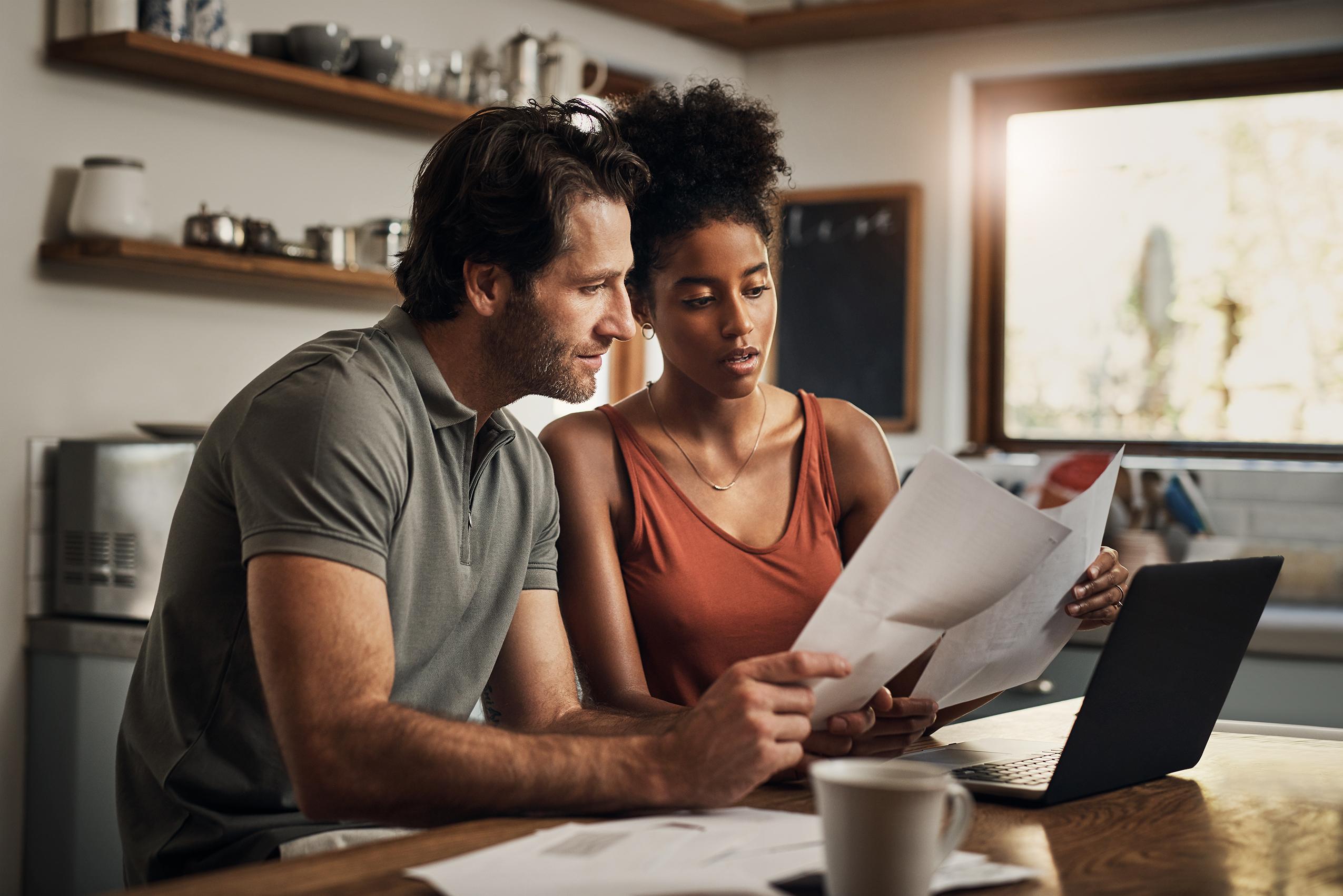 Couple looking at bills at table
