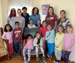 "Natalya B. Parris with her artwork ""Natalya's Flowers"", her students (5– 9 year old) from ""Art Around the World"" camp April 6 – 10, 2015 and volunteers  at the GFAA exhibit on 4/6/2015"