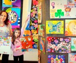 Instructor Natalya B. Parris with her student and student's art at the art show and reception on April 1st; Exploring the World Through Art Spring Break Camp March 28 - April 1, 2016