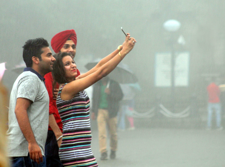 selfie - Indian teenagers taking a rain-drenched selfie in New Delhi. (Photo.. IANS)