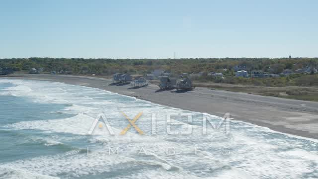 Flying by oceanfront homes, waves crashing on beach, Scituate, Massachusetts Aerial Stock Footage | AX143_034