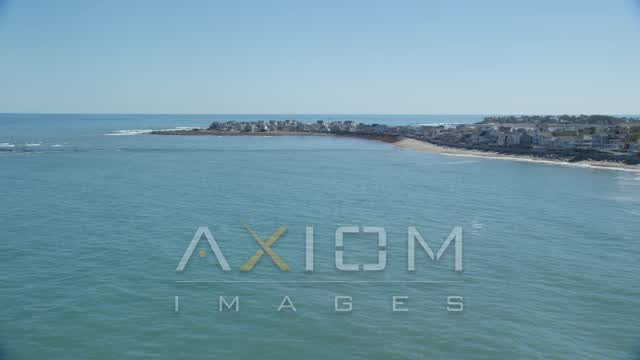 Fly low over ocean, approaching beach, homes, Scituate, Massachusetts Aerial Stock Footage | AX143_037