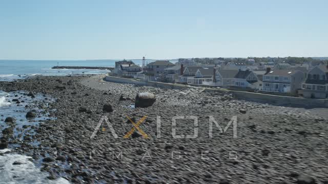 Flying by beach, oceanfront homes, Old Scituate Light, Scituate, Massachusetts Aerial Stock Footage | AX143_039