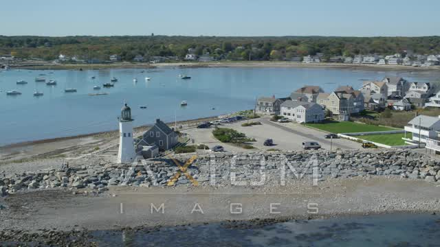 Orbiting a beach, oceanfront homes, Old Scituate Light, Scituate, Massachusetts Aerial Stock Footage AX143_041