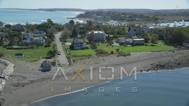 Flying by rocky beach, oceanfront homes, Scituate, Massachusetts Aerial Stock Footage | AX143_042