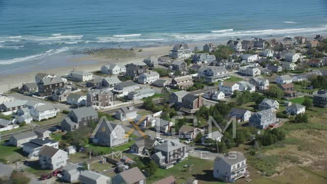 Flying by oceanfront homes, waves crashing, Marshfield, Massachusetts Aerial Stock Footage | AX143_055