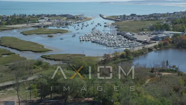 Flying over a small marina, fighting boats, Marshfield, Massachusetts Aerial Stock Footage | AX143_061