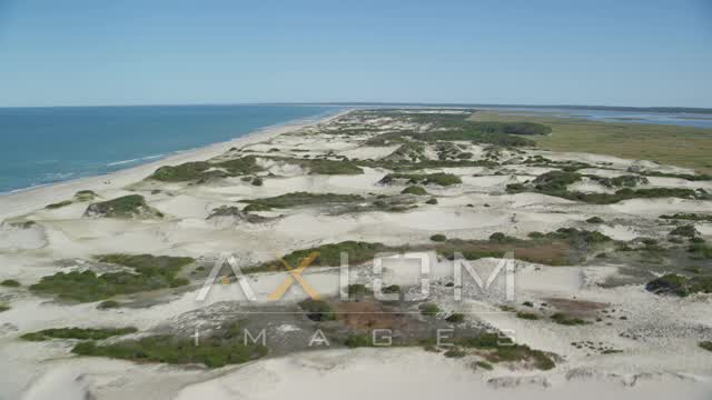 Flying over sand dunes, beach, approach isolated home, Barnstable, Massachusetts Aerial Stock Footage | AX143_135
