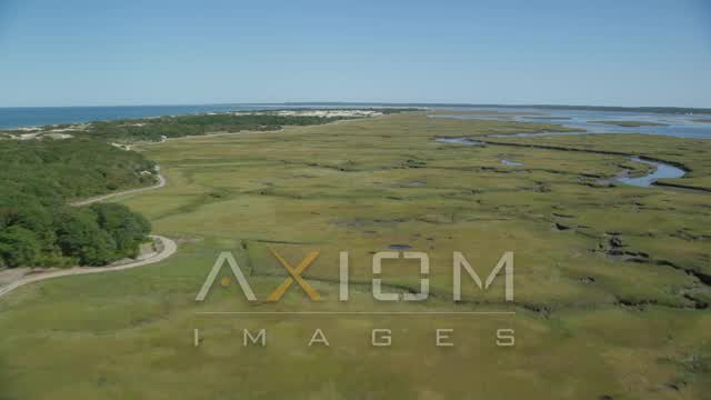 Fly over marshland, by isolated homes, coastal road, Barnstable, Massachusetts Aerial Stock Footage | AX143_136