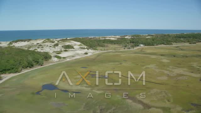 Flying by marshland, isolated homes, coastal road, Barnstable, Massachusetts Aerial Stock Footage | AX143_137