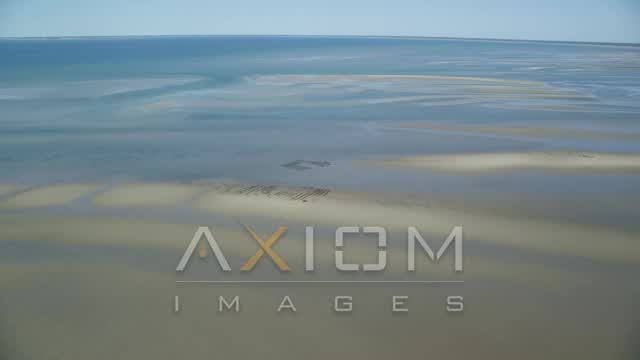 Flying by oyster farming on sand bars, low tide, Cape Cod, Dennis, Massachusetts Aerial Stock Footage | AX143_171