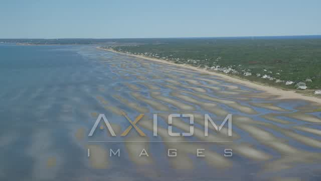 Flying over sand bars, approaching small coastal town, Eastham, Massachusetts Aerial Stock Footage | AX143_181