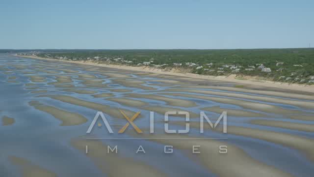 Flying over sand bars and by beachfront homes, Eastham, Massachusetts Aerial Stock Footage | AX143_183