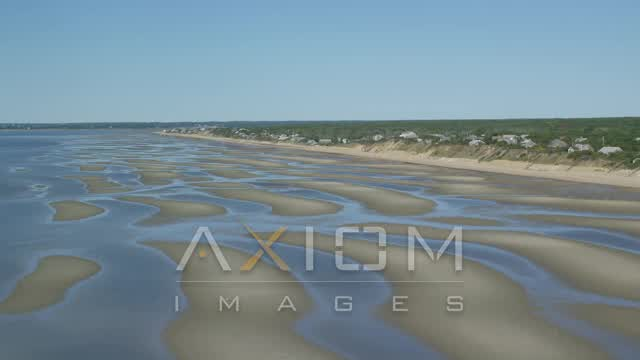 Flying over sand bars, by beachfront homes, Eastham, Massachusetts Aerial Stock Footage | AX143_184