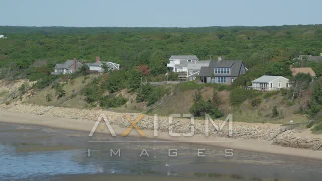 Flying by hilltop, beachfront hoes, Cape Cod, Eastham, Massachusetts Aerial Stock Footage | AX143_186