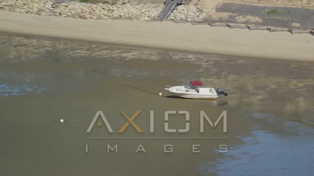 Flying by beached fishing boat on sandbar, Cape Cod, Eastham, Massachusetts Aerial Stock Footage | AX143_187
