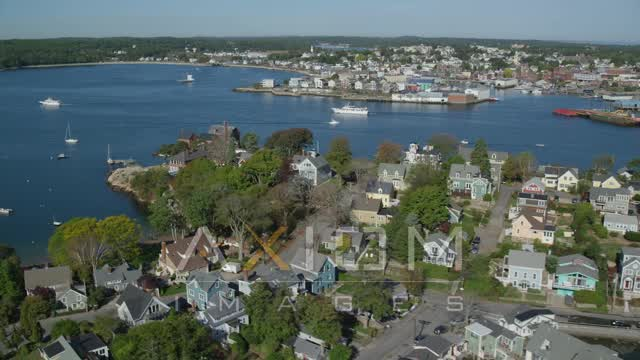 Flying by coastal town, revealing a small factory, boats, Gloucester, Massachusetts Aerial Stock Footage | AX147_097
