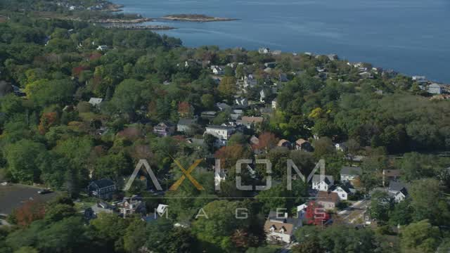 Small coastal town among trees in autumn, Gloucester, Massachusetts Aerial Stock Footage | AX147_133