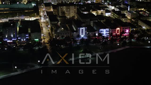 South Beach Hotels and Cafes with Bright Lights at Nighttime Aerial Stock Footage | AX23_072