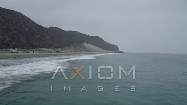 Flying low over Pacific Ocean waves and fly toward the end of a beach, Malibu, California Aerial Stock Footage | AX42_065