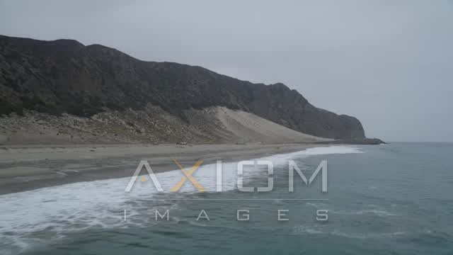 Fly low over ocean waves crashing into a beach near beach-goers and Highway 1 with light traffic, Malibu, California Aerial Stock Footage | AX42_066