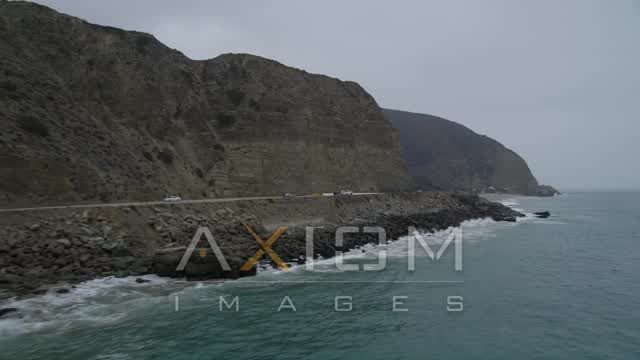 Fly low beside Highway 1 with light traffic to reveal a beach, Malibu, California Aerial Stock Footage | AX42_068