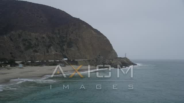 Low altitude approach to waves crashing against the coast, Malibu, California Aerial Stock Footage | AX42_069