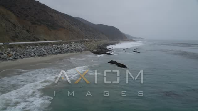 Flying low over waves rolling toward the coast and Highway 1, Malibu, California Aerial Stock Footage | AX42_073