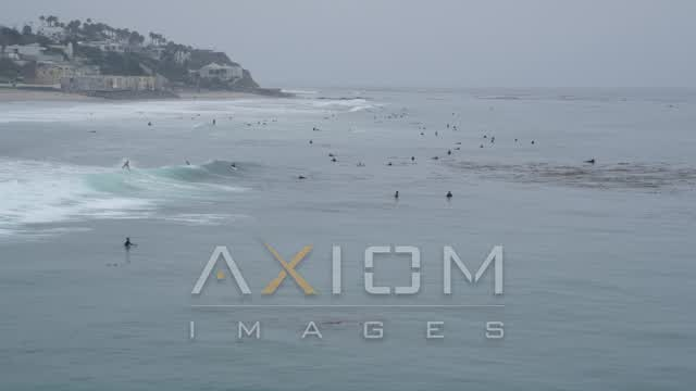Approach surfers in the Pacific Ocean off the coast of Malibu, California Aerial Stock Footage | AX42_077