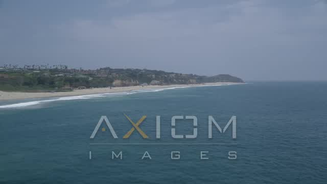 Flying over the Pacific Ocean and by a beach on the way to Point Dume, Malibu, California Aerial Stock Footage | AX42_084