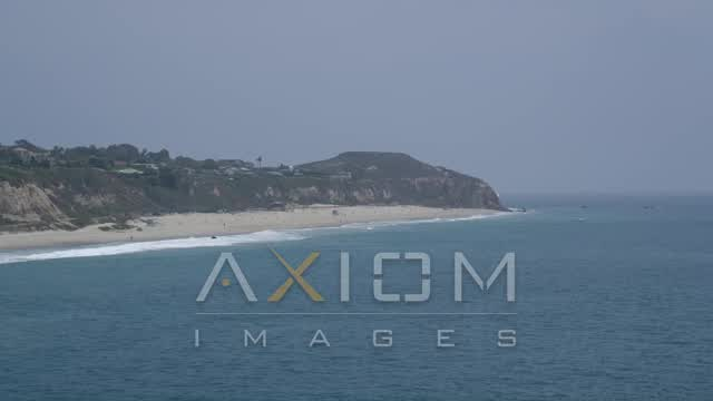 Flyby a beach by Point Dume in Malibu, California Aerial Stock Footage | AX42_085