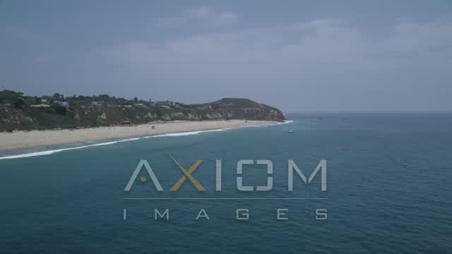 A sparsely populated beach and Point Dume, seen from the Pacific Ocean, Malibu, California Aerial Stock Footage | AX42_086