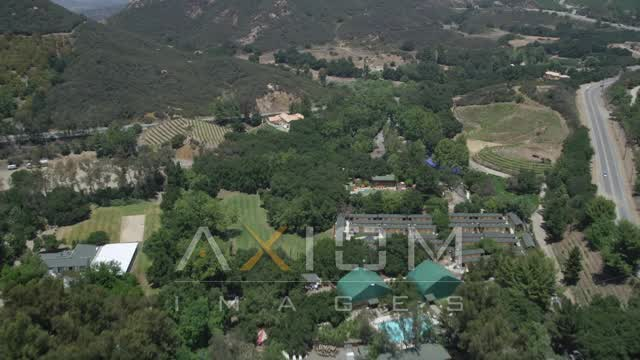 Flying over mansions, vineyards, and a country road in Malibu, California Aerial Stock Footage | AX42_100