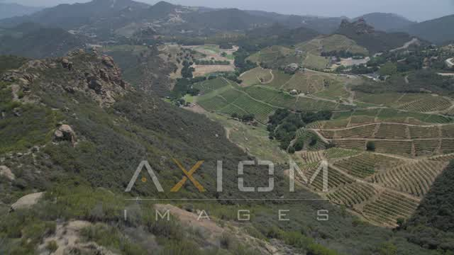 Approach and fly over rock formations to reveal hilly vineyards, Malibu, California Aerial Stock Footage | AX42_104