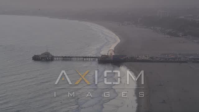 Santa Monica Pier at Sunset with People Walking the Beach Aerial Stock Footage | AX69_028