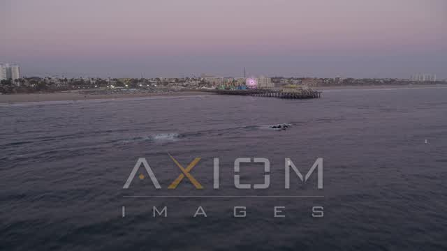 Fly Low Over the Ocean, and Tilt to Reveal and Approach Santa Monica Pier at Sunset Aerial Stock Footage | AX69_046