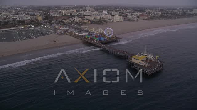 Approach Santa Monica Pier at Sunset and Tilt to a Bird's Eye View Aerial Stock Footage | AX69_047