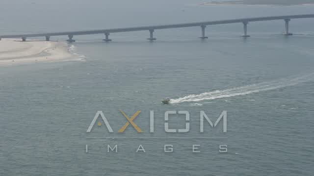 A fishing boat speeding across Great Egg Harbor Inlet near Ocean City Aerial Stock Footage | AX71_216