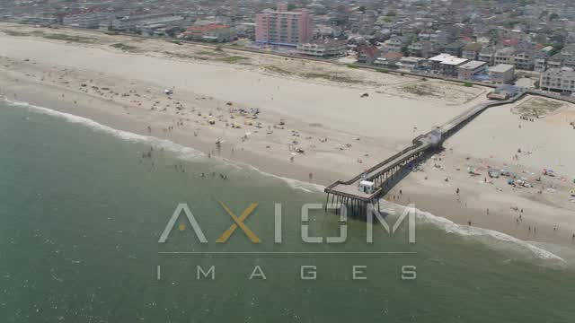 A pier and beach goers in Ocean City, New Jersey Aerial Stock Footage | AX71_223