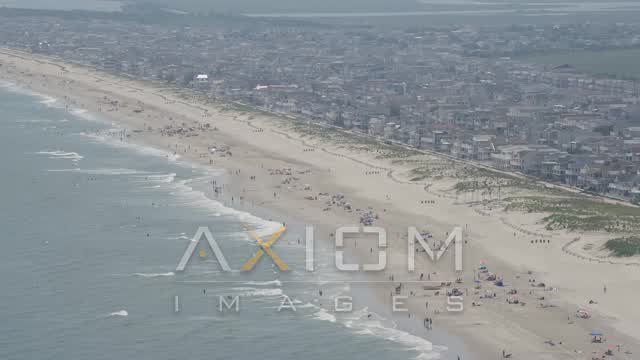 Beach goers and beachfront homes in Ocean City, New Jersey Aerial Stock Footage | AX71_228