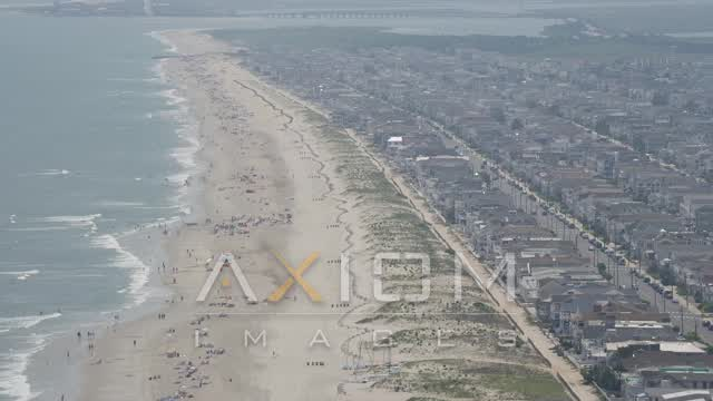 Beach goers and beachfront homes in Ocean City, New Jersey Aerial Stock Footage | AX71_229